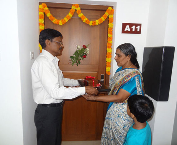 Keys being handed over to Mrs. Laksmi of apartment A 11