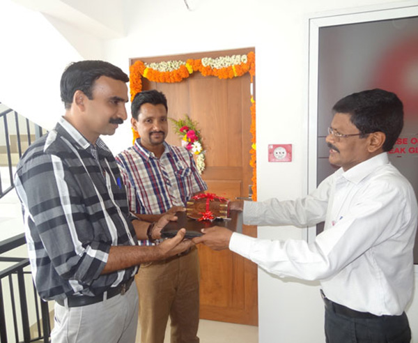 Keys being handed over to Mr. Vinod Kumar & Mr. Santhosh Kumar of apartment B 9