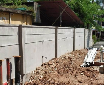 Shows compound wall masonry work nearing completion.